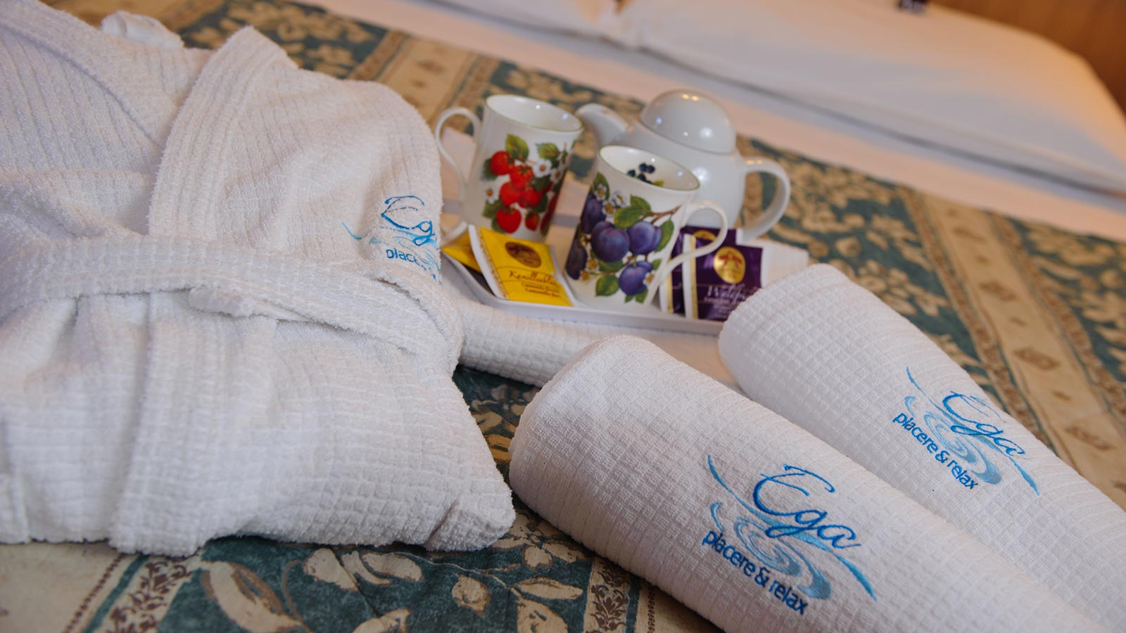 towels and bathrobe on a hotel room bed at La Serenella in Moena